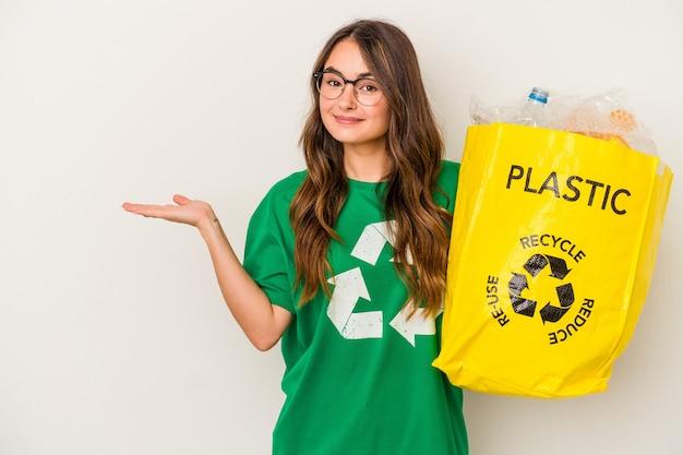 Joven mujer caucásica reciclando un lleno de plástico aislado sobre fondo blanco mostrando un espacio de copia en una palma y sosteniendo otra mano en la cintura.