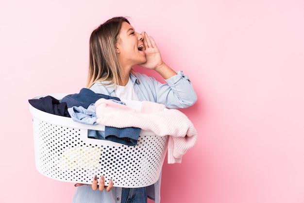 Joven mujer caucásica recogiendo una ropa sucia gritando y sosteniendo la palma cerca de la boca abierta.