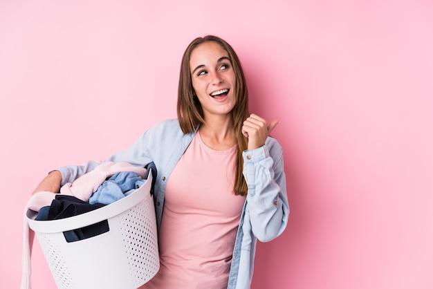 Joven mujer caucásica recogiendo ropa sucia puntos aislados con el dedo pulgar, riendo y sin preocupaciones.
