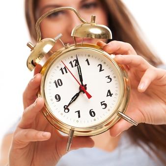 Joven mujer caucásica con reloj despertador