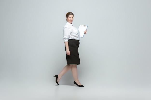 Joven mujer caucásica en ropa casual sobre fondo gris bodypositive personaje femenino más tamaño