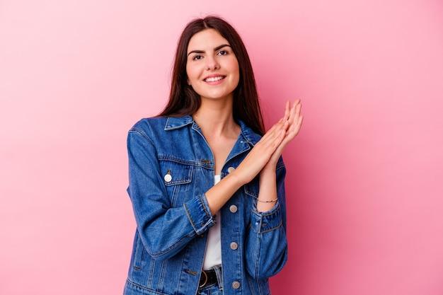 Joven mujer caucásica en rosa sintiéndose enérgica y cómoda, frotándose las manos con confianza.