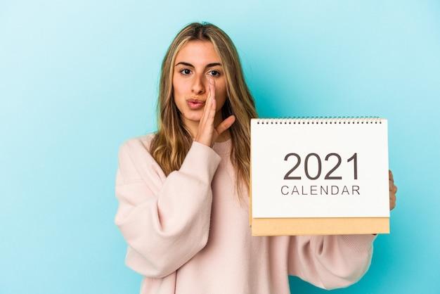 Joven mujer caucásica rubia agujereando un calendario aislado está diciendo una noticia secreta de frenado caliente y mirando a un lado