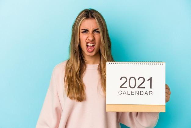 Joven mujer caucásica rubia agujereando un calendario aislado gritando muy enojado y agresivo.