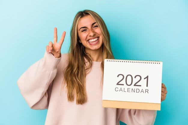 Joven mujer caucásica rubia agujereando un calendario aislado mostrando el número dos con los dedos