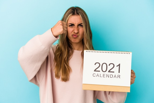 Joven mujer caucásica rubia agujereando un calendario aislado mostrando el puño a la cámara, expresión facial agresiva.