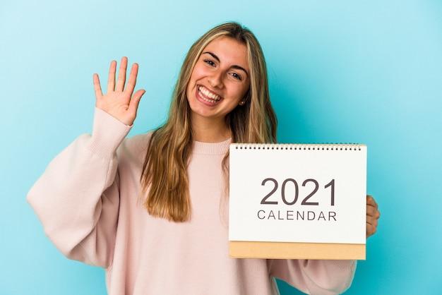 Joven mujer caucásica rubia agujereando un calendario aislado sonriendo alegre mostrando el número cinco con los dedos.