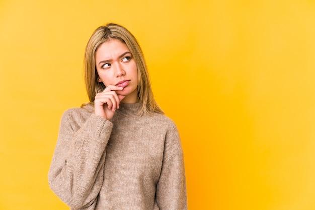 Joven mujer caucásica rubia aislada en amarillo mirando hacia los lados con expresión dudosa y escéptica.