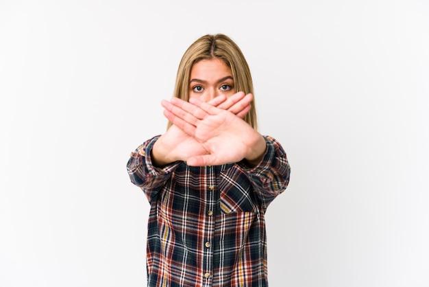 Joven mujer caucásica rubia aislada haciendo un gesto de negación