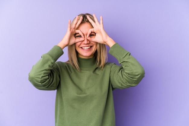 Joven mujer caucásica rubia aislada mostrando bien firmar sobre los ojos