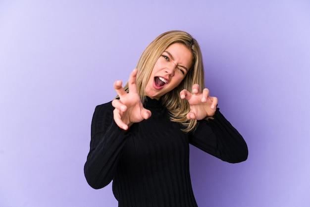 Joven mujer caucásica rubia aislada mostrando garras imitando un gato, gesto agresivo.