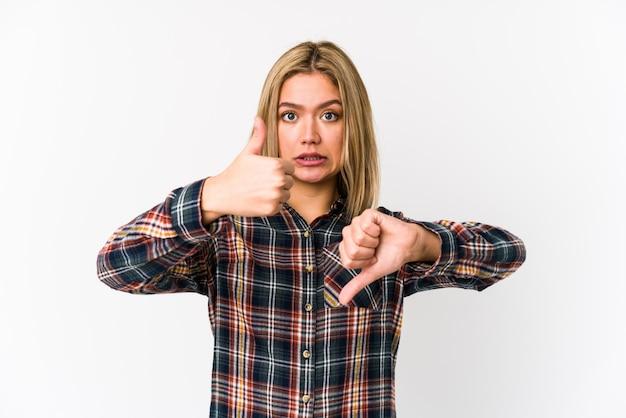 Joven mujer caucásica rubia aislada mostrando los pulgares hacia arriba y hacia abajo, difícil elegir el concepto