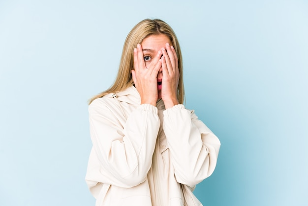 Joven mujer caucásica rubia aislada parpadeo a través de los dedos asustada y nerviosa.