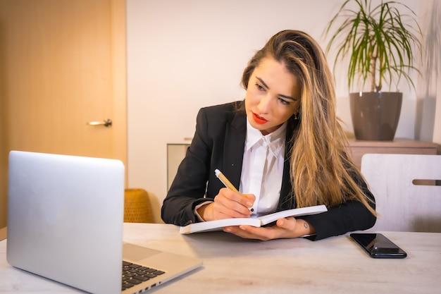 Joven mujer caucásica rubia tomando notas en la reunión de videollamadas en línea
