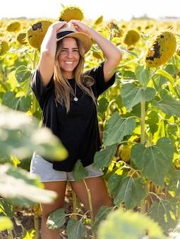 Joven mujer caucásica con sombrero caminando en un campo de girasoles en un día soleado