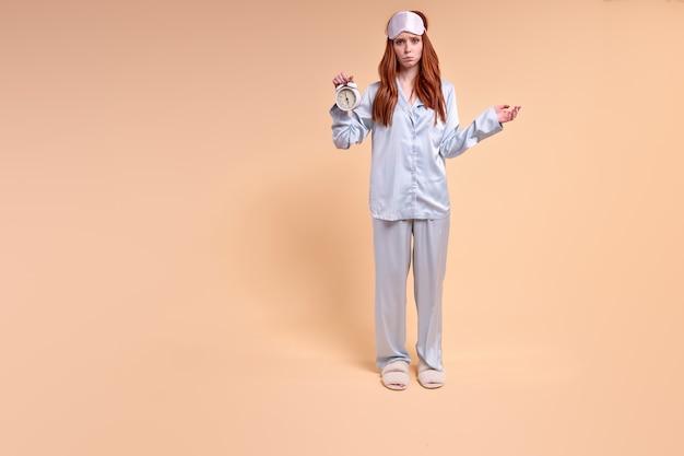 Joven mujer caucásica soñolienta sobre fondo beige aislado en pijama sosteniendo reloj con expresión decepcionada molesta posando dama confundida con antifaz en la frente mujer no tiene suficiente sueño