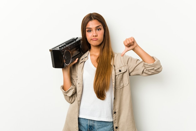 Joven mujer caucásica sosteniendo un blaster guetto mostrando un gesto de aversión, pulgares hacia abajo. concepto de desacuerdo.