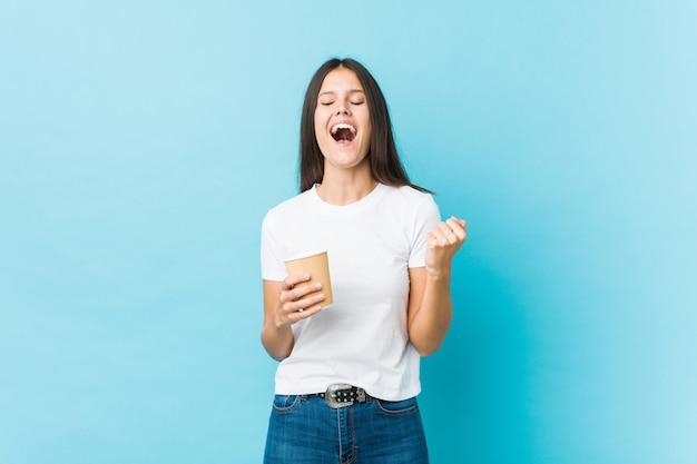 Joven mujer caucásica sosteniendo un café para llevar animando despreocupado y emocionado