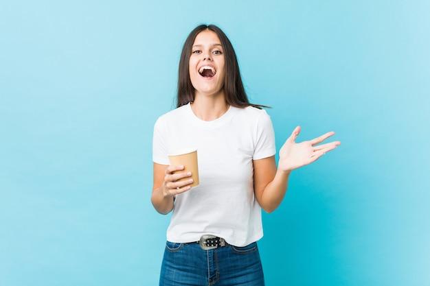Joven mujer caucásica sosteniendo un café para llevar celebrando una victoria o éxito