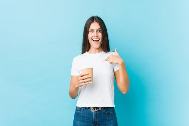 Joven mujer caucásica sosteniendo un café para llevar sorprendido apuntando a sí misma