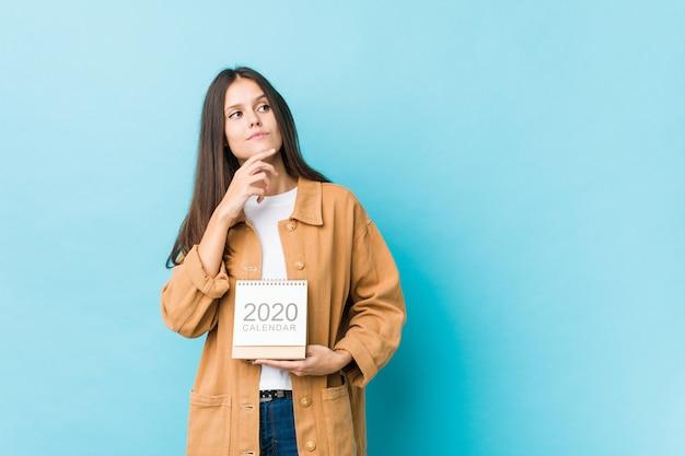 Joven mujer caucásica sosteniendo un calendario 2020 mirando hacia los lados con expresión dudosa y escéptica.