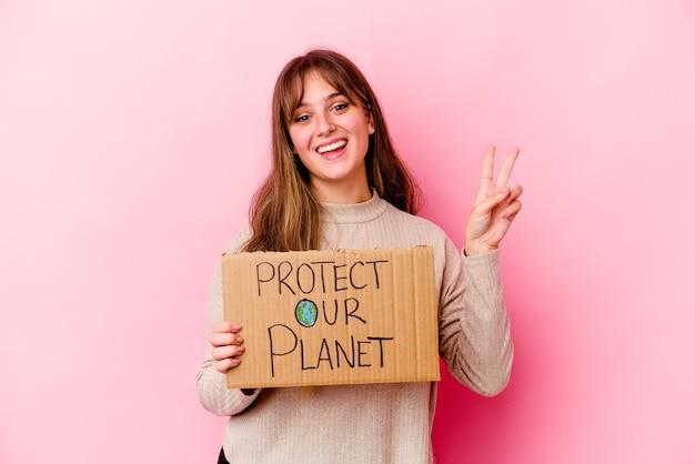 Joven mujer caucásica sosteniendo un cartel de proteger nuestro planeta aislado alegre y despreocupado mostrando un símbolo de paz con los dedos.