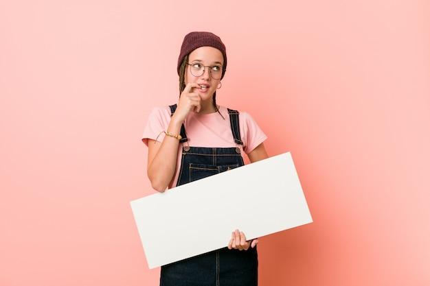 Joven mujer caucásica sosteniendo un cartel relajado pensando en algo mirando un espacio de copia.