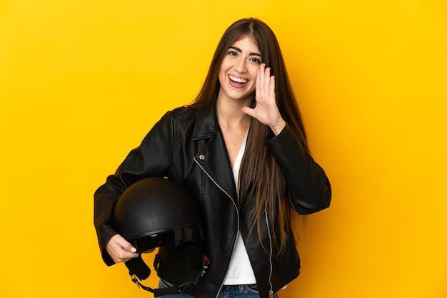 Joven mujer caucásica sosteniendo un casco de motocicleta aislado en la pared amarilla gritando con la boca abierta