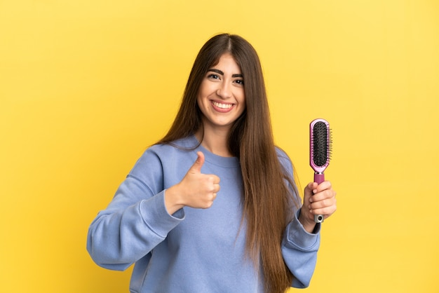 Joven mujer caucásica sosteniendo el cepillo para el cabello aislado sobre fondo azul dando un pulgar hacia arriba gesto