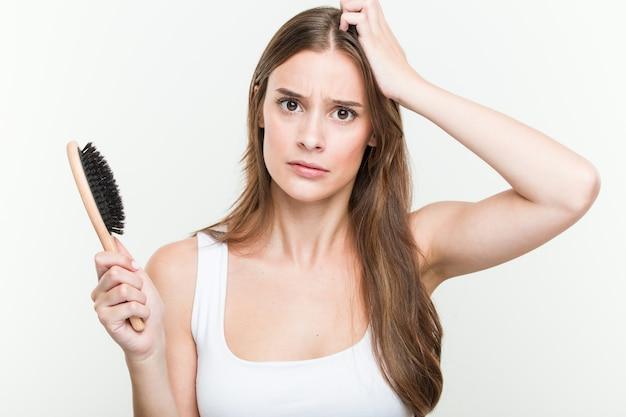 Joven mujer caucásica sosteniendo un cepillo de pelo se sorprendió, ella ha recordado una reunión importante.