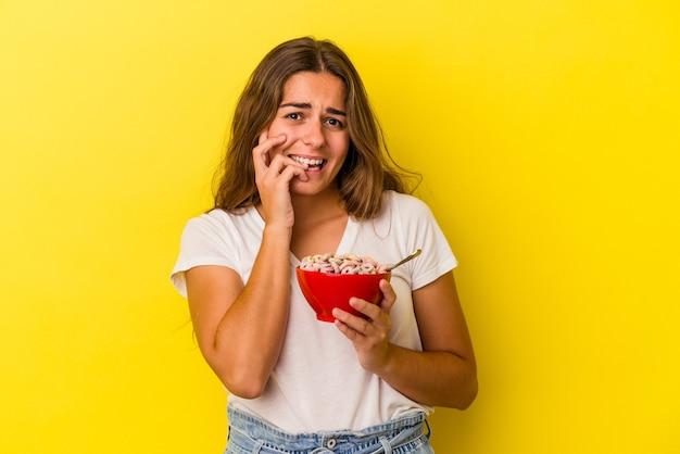 Joven mujer caucásica sosteniendo cereales aislados sobre fondo amarillo mordiéndose las uñas, nerviosa y muy ansiosa.