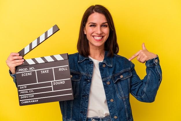 Joven mujer caucásica sosteniendo una claqueta aislada sobre fondo amarillo persona apuntando con la mano a un espacio de copia de camisa, orgulloso y seguro