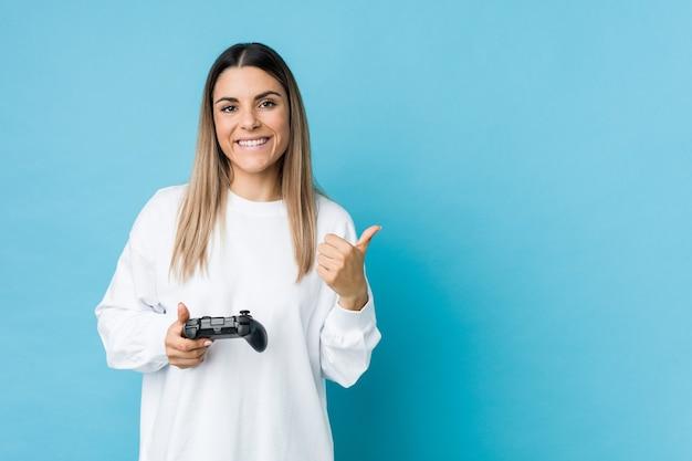 Joven mujer caucásica sosteniendo un controlador de juego sonriendo y levantando el pulgar