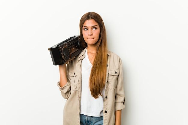 Joven mujer caucásica sosteniendo un guetto blaster confundido, se siente dudoso e inseguro.