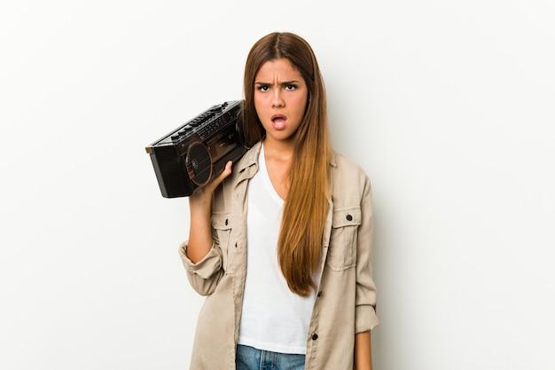 Joven mujer caucásica sosteniendo un guetto blaster gritando muy enojado y agresivo.