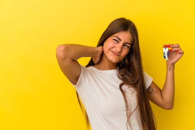 Joven mujer caucásica sosteniendo una llave de casa aislada sobre fondo amarillo tocando la parte posterior de la cabeza, pensando y haciendo una elección.