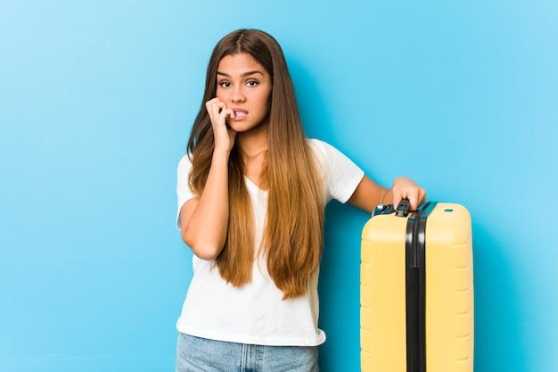 Joven mujer caucásica sosteniendo una maleta de viaje mordiéndose las uñas, nerviosa y muy ansiosa.