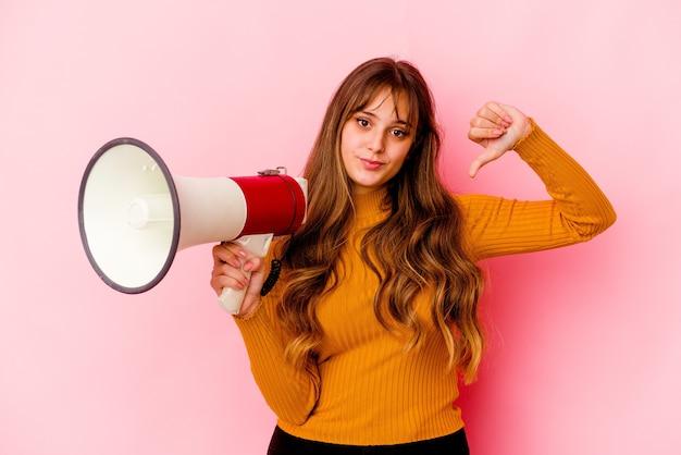 Joven mujer caucásica sosteniendo un megáfono aislado mostrando un gesto de aversión, pulgares hacia abajo. concepto de desacuerdo.