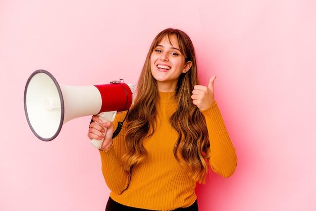 Joven mujer caucásica sosteniendo un megáfono aislado sonriendo y levantando el pulgar