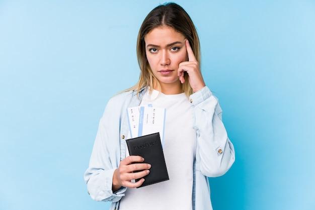 Joven mujer caucásica sosteniendo un pasaporte aislado señalando el templo con el dedo, pensando, centrado en la tarea.