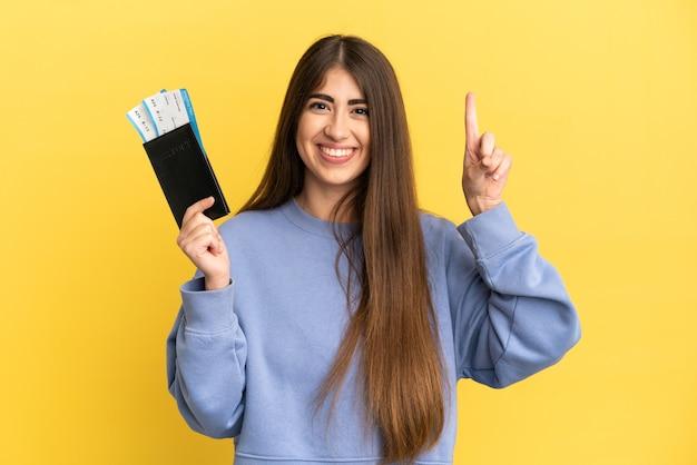 Joven mujer caucásica sosteniendo un pasaporte aislado sobre fondo amarillo apuntando hacia una gran idea