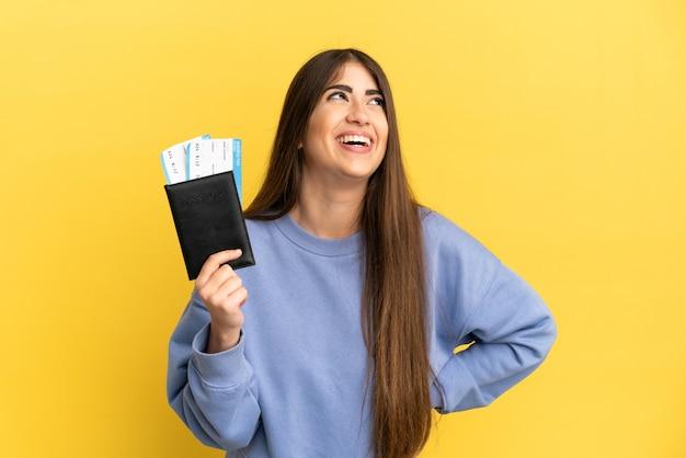 Joven mujer caucásica sosteniendo un pasaporte aislado sobre fondo amarillo riendo