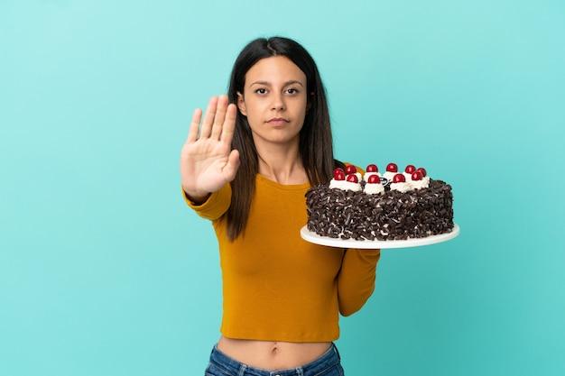 Joven mujer caucásica sosteniendo pastel de cumpleaños aislado sobre fondo azul haciendo gesto de parada