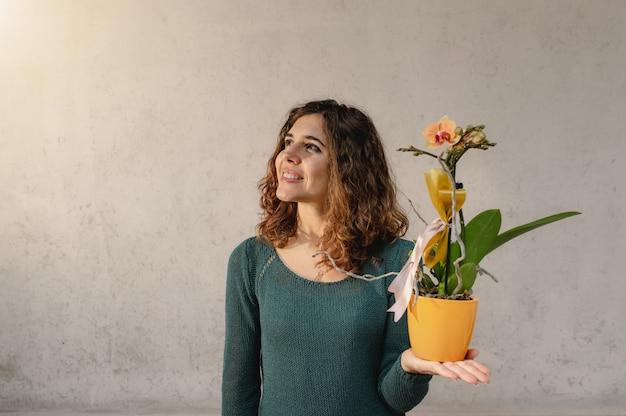 Joven mujer caucásica sosteniendo una pequeña planta de orquídea amarilla mirando hacia arriba sonriendo.