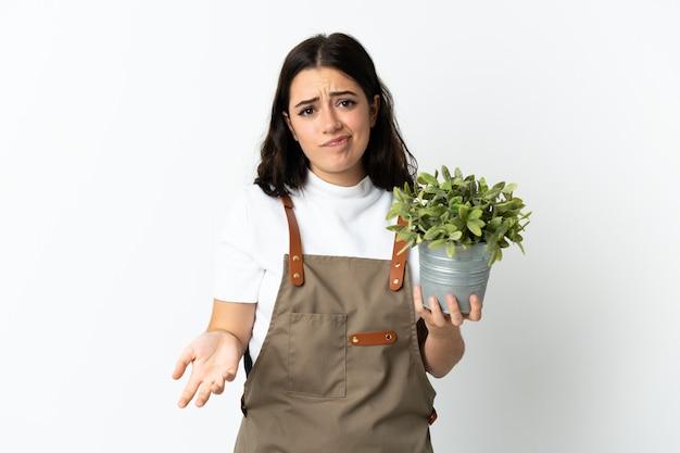Joven mujer caucásica sosteniendo una planta aislada en la pared blanca haciendo gesto de dudas mientras levanta los hombros