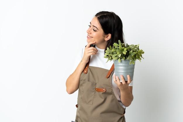Joven mujer caucásica sosteniendo una planta aislada sobre fondo blanco pensando en una idea y mirando de lado