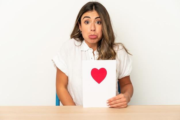Joven mujer caucásica sosteniendo una tarjeta del día de san valentín aislada se encoge de hombros y abre los ojos confundidos.