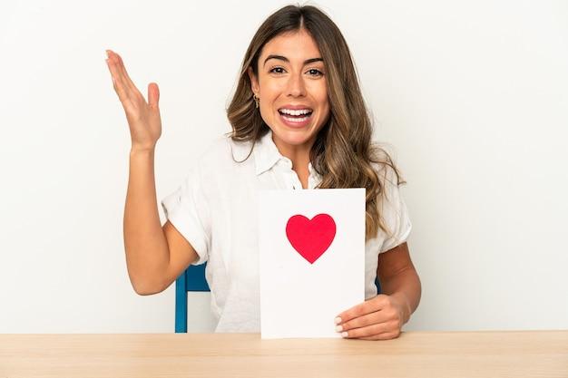 Joven mujer caucásica sosteniendo una tarjeta del día de san valentín aislada recibiendo una agradable sorpresa, emocionada y levantando las manos.