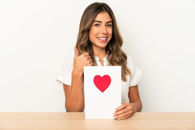 Joven mujer caucásica sosteniendo una tarjeta del día de san valentín aislada sonriendo y levantando el pulgar hacia arriba