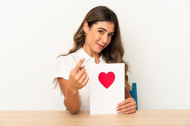 Joven mujer caucásica sosteniendo una tarjeta de san valentín aislada apuntando con el dedo hacia usted como si estuviera invitando a acercarse.